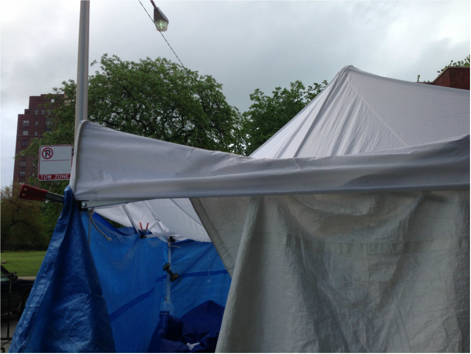 Notice how the tents stretched under the weight of the rain. Also please note the use of gallon milk jugs to weigh down the one tent on the right. : fair tent - memphite.com